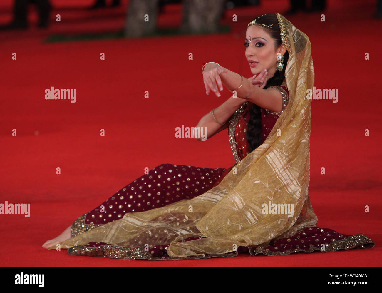 An Indian dancer performs on the red carpet before a