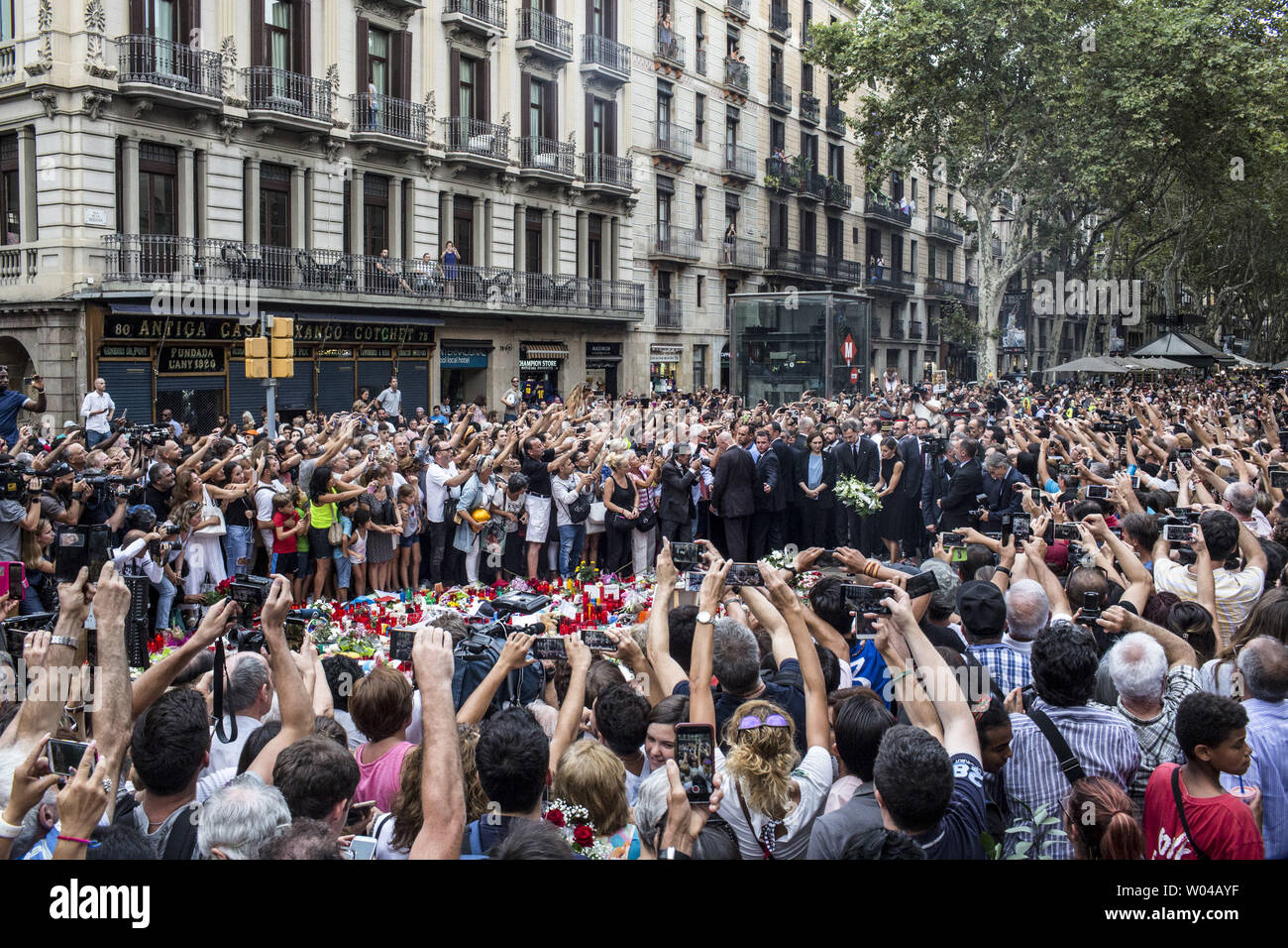 People take photos as Spain's King Felipe and Queen Letizia paying respect at a memorial tribute of flowers, messages and candles to the van attack victims in Las Ramblas promenade, Barcelona, Spain, on August 19, 2017, two days after a van ploughed into the crowd, killing 14 persons and injuring over 100. Drivers have plowed on August 17, 2017 into pedestrians in two quick-succession, separate attacks in Barcelona and another popular Spanish seaside city, leaving 14 people dead and injuring more than 100 others. photo by Angel Garcia/ UPI Stock Photo