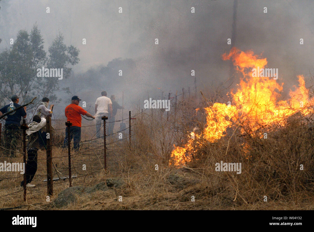 Jerry Newman (center in orange) uses hose to defend his property in Lakeside, California on October 26, 2003. Newman's residence was saved by family and neighbors as fire crews were stretched extremely thin. Fires spread from Ramona southwest to enter San Diego city limits consuming 80,000 acres, burning 50 buildings, and leaving 3 fatalities to date.  (UPI Photo/Tom Theobald) Stock Photo