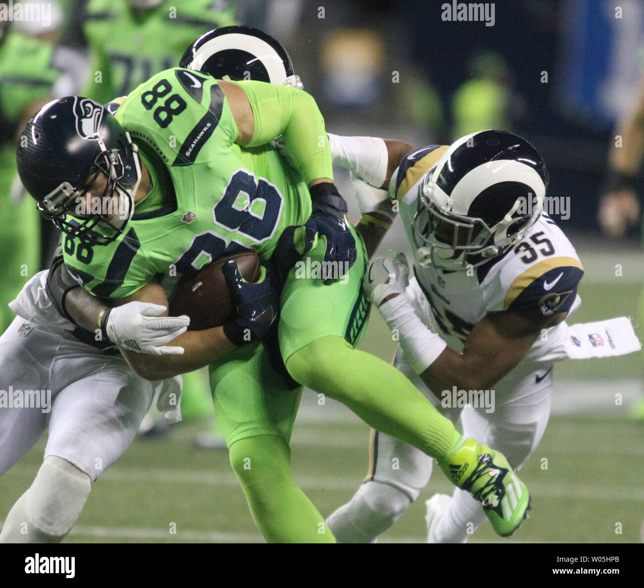 Seattle Seahawks Tight End Jimmy Graham 88 Fights Through The Tackles Of Los Angeles Rams Defensive Back Michael Jordan 35 And Los Angeles Rams Defensive Back Cody Davis 38 After Catching A