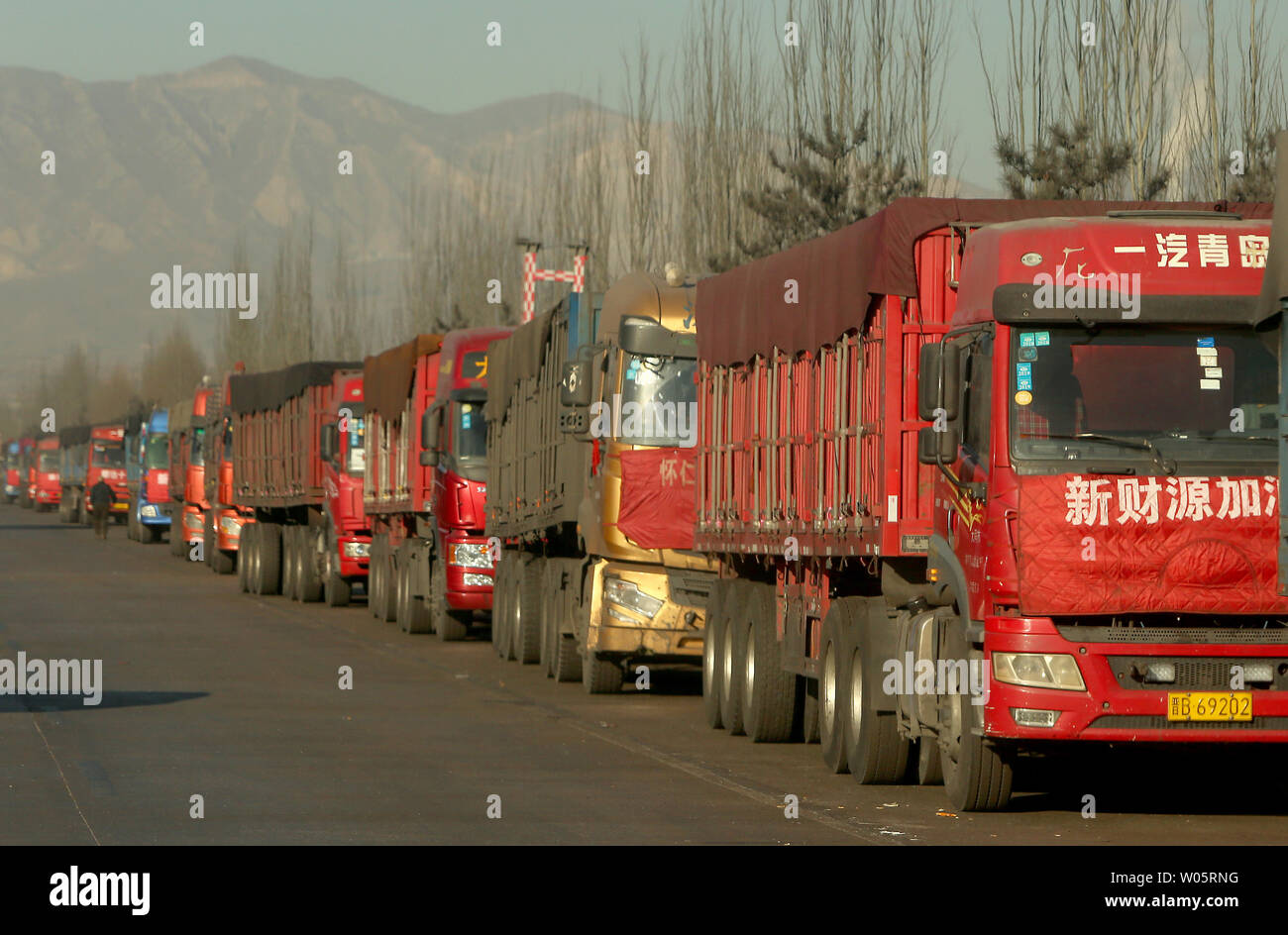 Coal trucks parked outside a mine wait for the green-light to pickup a load of coal in Datong, Shanxi Province (China's coal country), on December 12, 2018.  China is the largest producer and consumer of coal in the world, making it the leading emitter of greenhouse gases from coal.  China burns much more coal than reported, which has continued to complicate climate talks.    Photo by Stephen Shaver/UPI.. Stock Photo