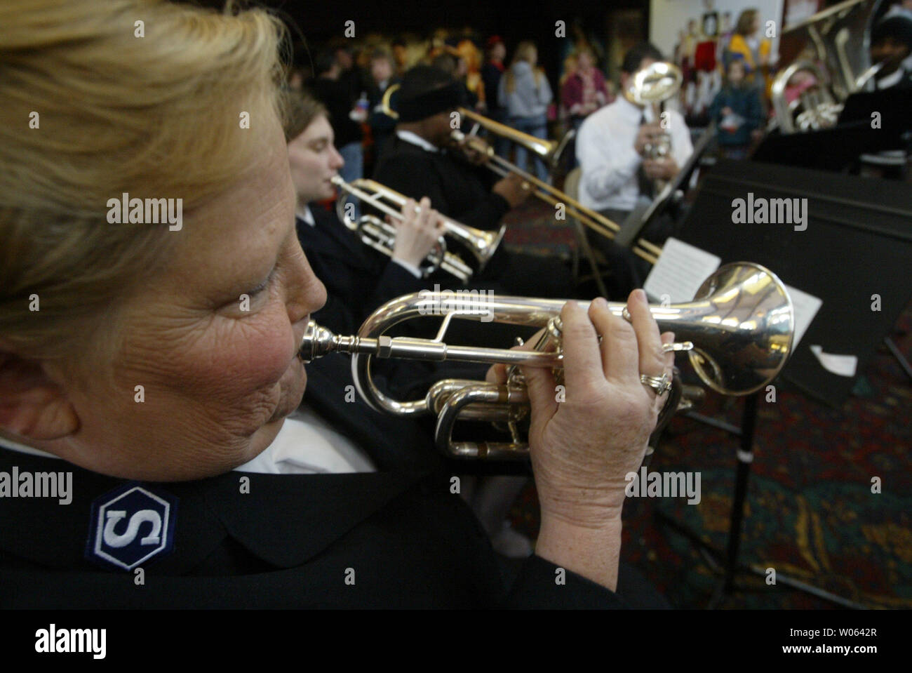 Salvation Army band member Linda Cooper plays her trumpet during the Wehrenberg Cans Film Festival at the Des Peres 14 Cine in Des Peres, Mo on December 3, 2005. Movie goers exchange canned goods for a movie ticket with the food going to feed the needy served by the St. Louis area Salvation Army. Last year the Wehrenberg Cans Film Festival yeilded 254 thousand cans in six hours. (UPI Photo/Bill Greenblatt) Stock Photo