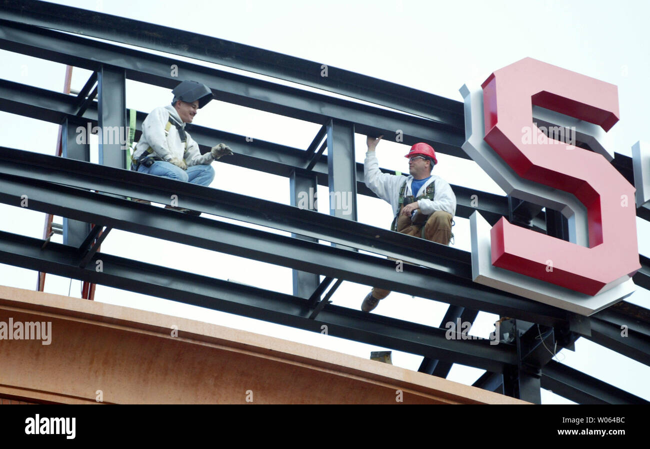 Welders wait atop the new Busch Stadium for the next letter as the main sign at the new St. Louis Cardinals home is installed in St. Louis on December 27, 2005. The Cardinals are expected to play their home opener in the new facility on April 10, 2006. (UPI Photo/Bill Greenblatt) - Stock Image
