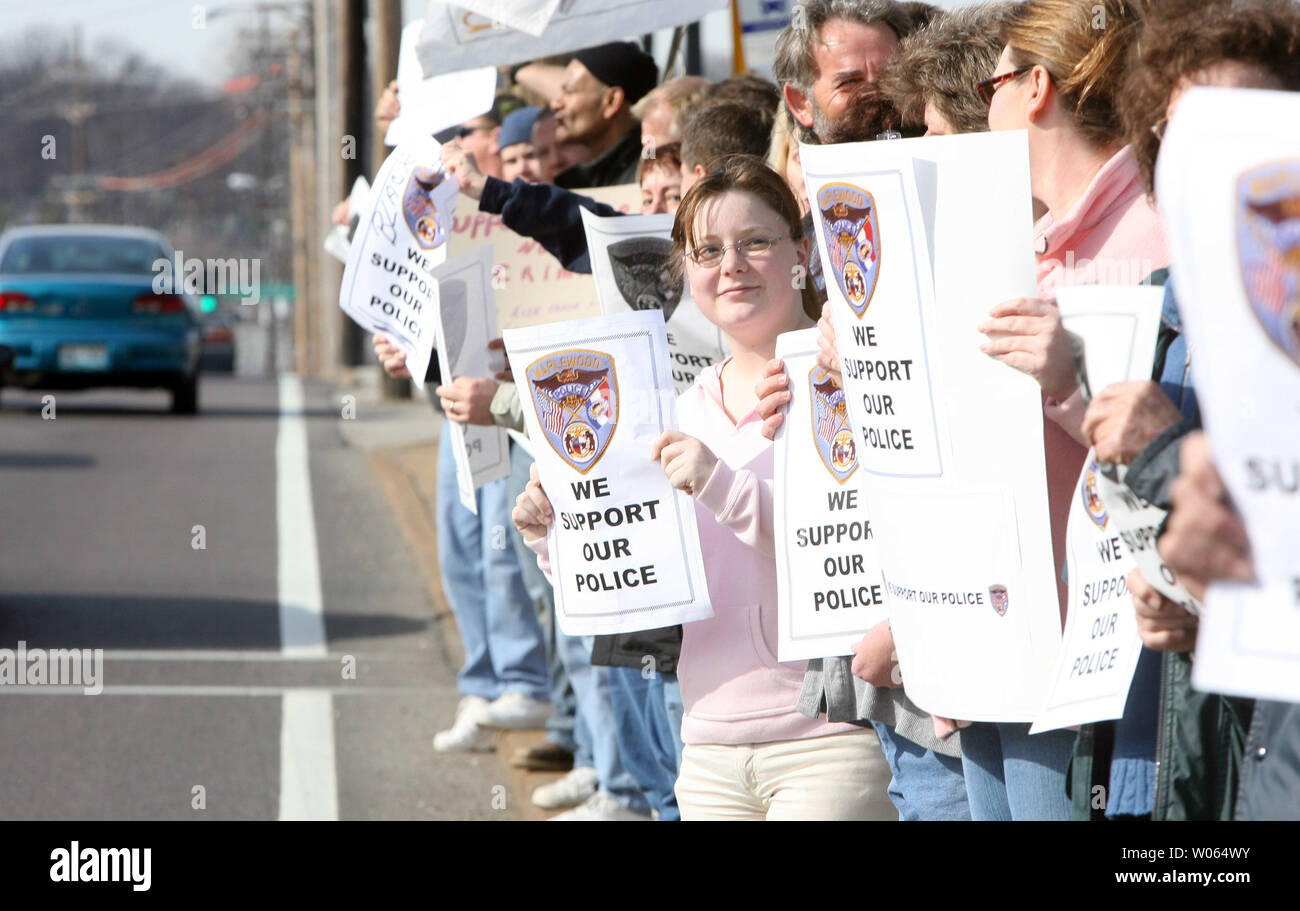 Protesters hold signs along a busy street in support of the four police officers accused of using excessive force during a recent arrest, at a protest in front of the Maplewood, Mo Police Department in Maplewood, Mo on February 3, 2006. The group, Coalition Against Police Crimes and Repression, are claiming that three Maplewood, Mo Police officers and one St. Louis Police officer, used poor judgement in the car chase and arrest of Edmun Burns on January 30. Burns, who left a Maplewood, Mo gas station without paying for gasoline, led police on a chase at speeds up to 80 miles per hour, into the - Stock Image