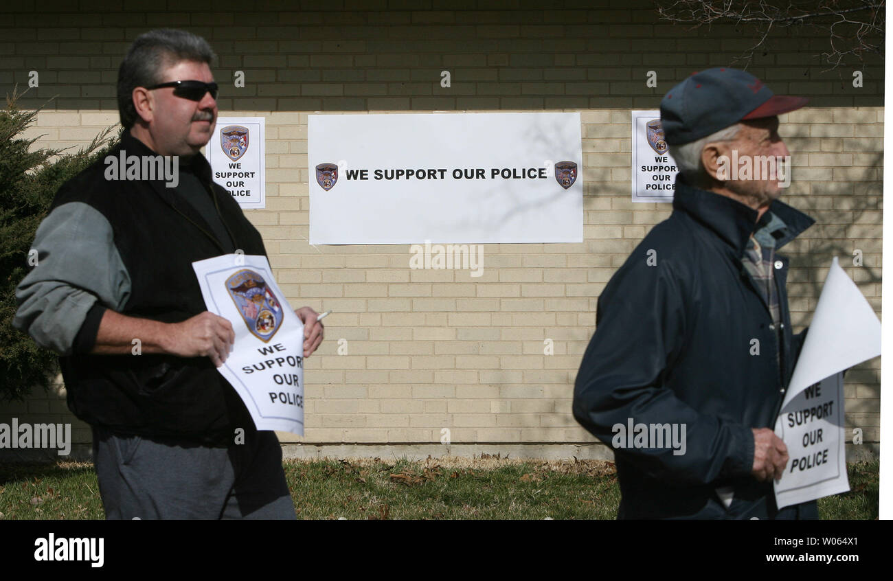 Protesters walk with signs in support of the four police officers accused of using excessive force during a recent arrest, at a protest in front of the Maplewood, Mo Police Department in Maplewood, Mo on February 3, 2006. The group, Coalition Against Police Crimes and Repression, are claiming that three Maplewood, Mo Police officers and one St. Louis Police officer, used poor judgement in the car chase and arrest of Edmun Burns on January 30. Burns, who left a Maplewood, Mo gas station without paying for gasoline, led police on a chase at speeds up to 80 miles per hour, into the City of St. Lo - Stock Image