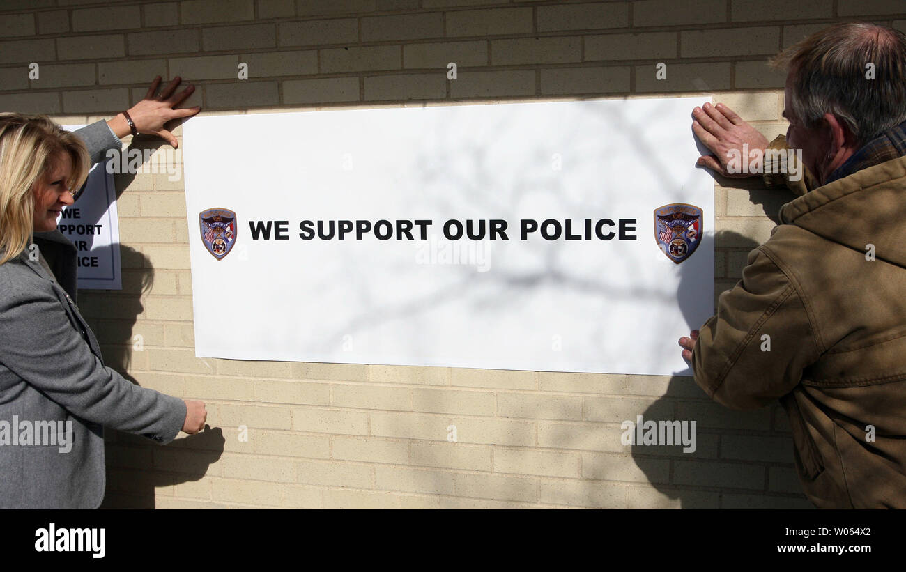 Theresa Arnett (L) and her brother-in-law Keith Arnett affix a sign to a building in support of the four police officers accused of using excessive force during a recent arrest, at a protest in front of the Maplewood, Mo Police Department in Maplewood, Mo on February 3, 2006. The group, Coalition Against Police Crimes and Repression, are claiming that three Maplewood, Mo Police officers and one St. Louis Police officer, used poor judgement in the car chase and arrest of Edmun Burns on January 30. Burns, who left a Maplewood, Mo gas station without paying for gasoline, led police on a chase at - Stock Image