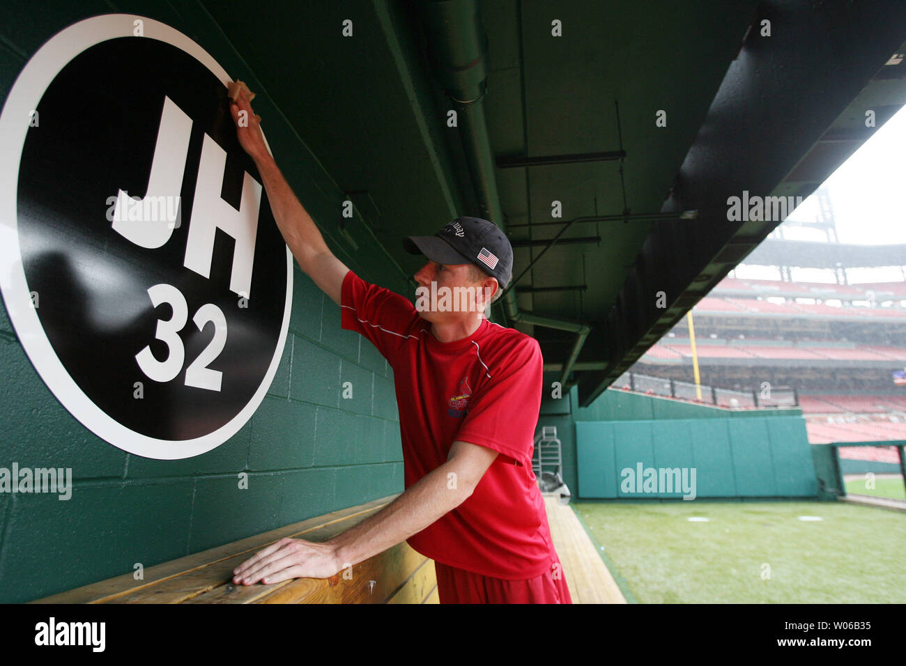 Busch Stadium grounds keeper Ryan Middleton wipes off a new sign in