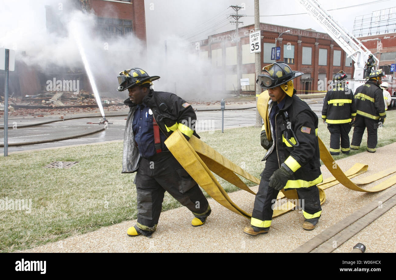 St  Louis firefighters drag hose up the street as fire