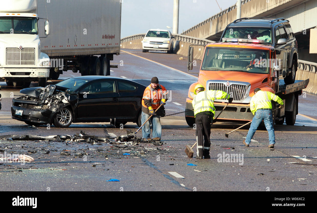 Workers attempt to clear debris and wrecked cars where an