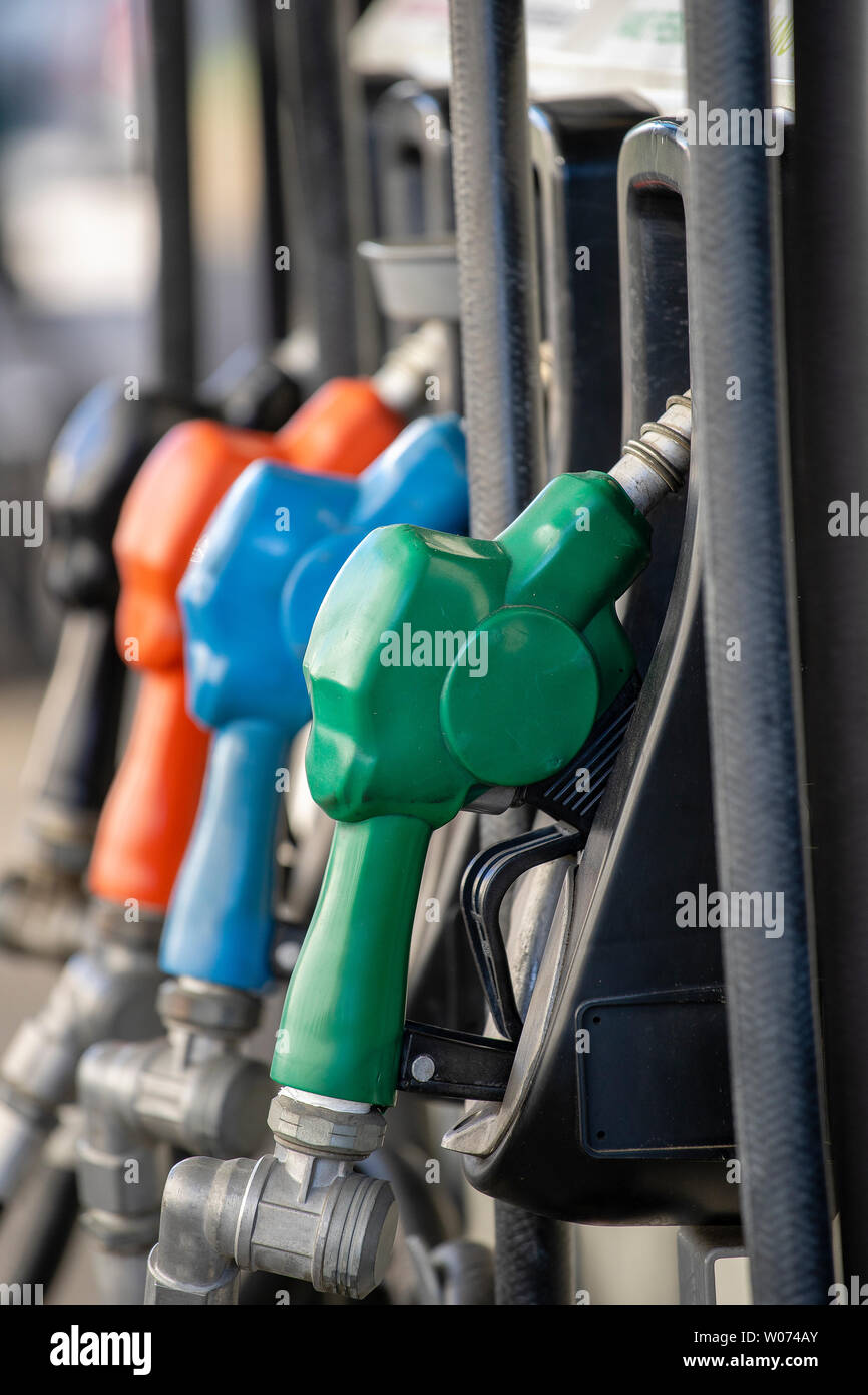 Close up of petroleum gasoline station service - oil refueling and refilling for car transportation concept. Petrol pump filling nozzles. Fuel at gas Stock Photo