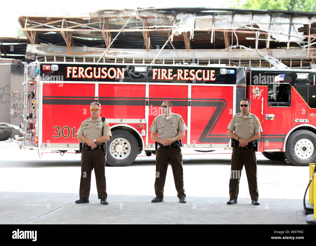 St. Louis County Police stand guard as firefighters return to the QuikTrip Gas station to put out hot spots following a night of looting, rioting and arsons in Ferguson, Missouri on August 11, 2014. People are upset because of the Ferguson Police shooting and death of an unarmed black teenager Michael Brown on August 9, 2014. In all about 20 businesses sustained damage after a candlelight vigil turned violent.   UPI/Bill Greenblatt Stock Photo