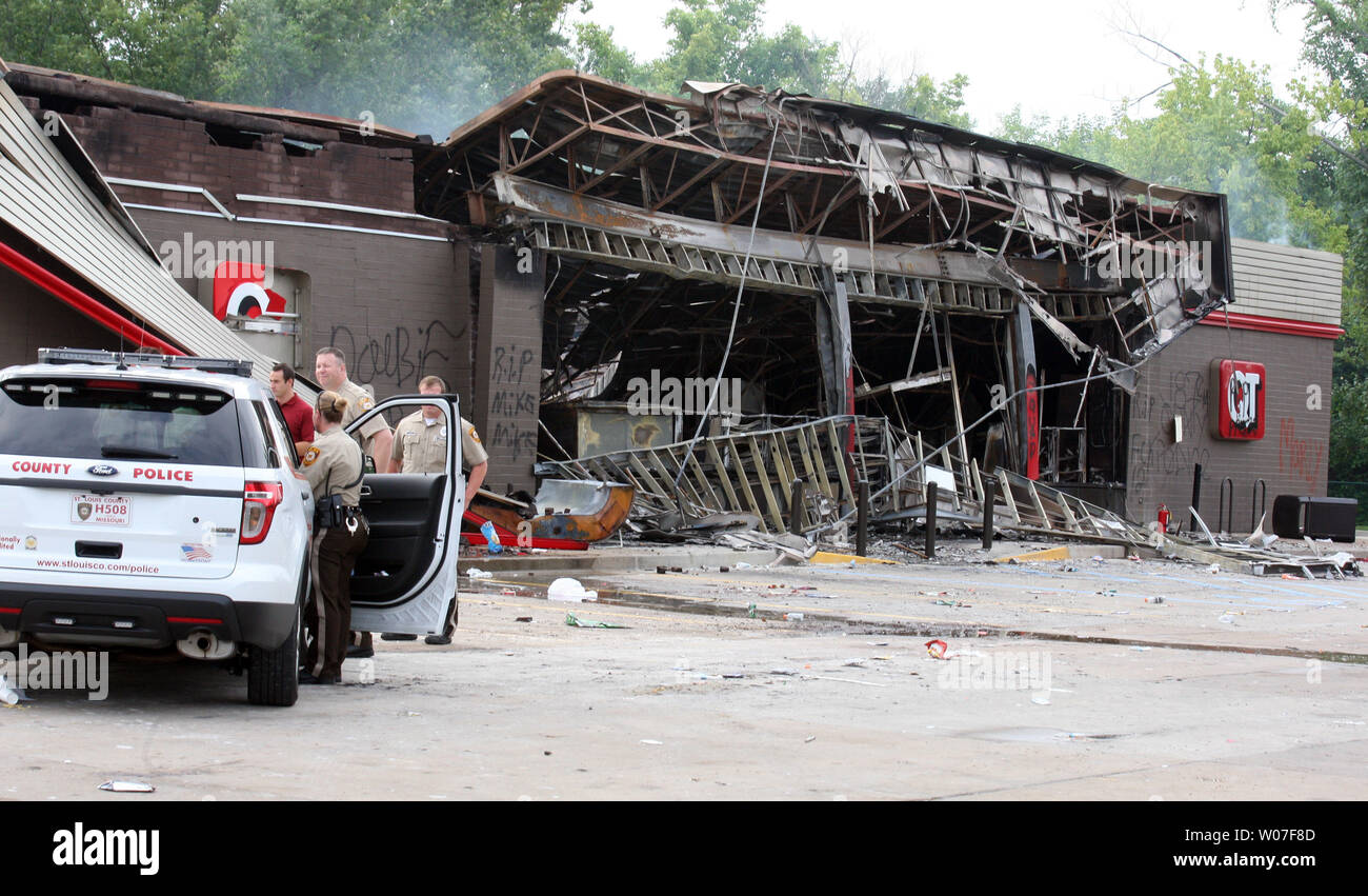 St. Louis County Police stand guard at a QuikTrip Gas station following a night of looting, rioting and arsons in Ferguson, Missouri on August 11, 2014. People are upset because of the Ferguson Police shooting and death of an unarmed black teenager Michael Brown on August 9, 2014. In all about 20 businesses sustained damage after a candlelight vigil turned violent.   UPI/Bill Greenblatt Stock Photo