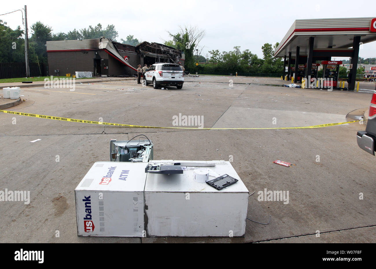 St. Louis County Police stand guard over a QuickTrip Gas staton that was burned, while a ATM machine lays in the parking lot following a night of looting, rioting and arsons in Ferguson, Missouri on August 11, 2014. People are upset because of the Ferguson Police shooting and death of an unarmed black teenager Michael Brown on August 9, 2014. In all about 20 businesses sustained damage after a candlelight vigil turned violent.   UPI/Bill Greenblatt Stock Photo