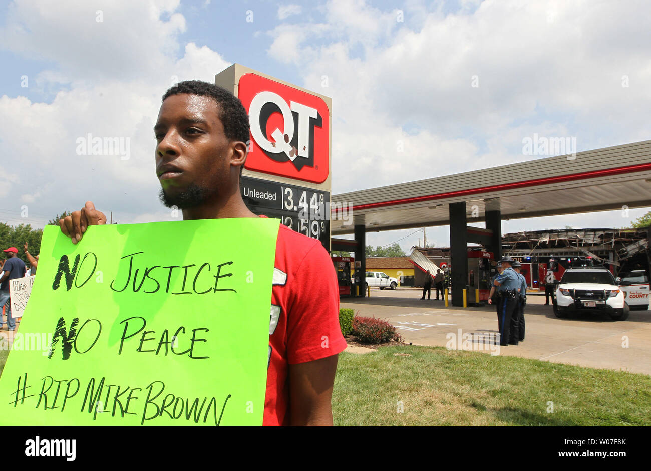 Protestor Allen Smith holds his sign up for passing traffic as he stands outside of the QuikTrip Gas station that was burned after a night of looting, rioting and arsons in Ferguson, Missouri on August 11, 2014. People are upset because of the Ferguson Police shooting and death of an unarmed black teenager Michael Brown on August 9, 2014. In all about 20 businesses sustained damage after a candlelight vigil turned violent.   UPI/Bill Greenblatt Stock Photo