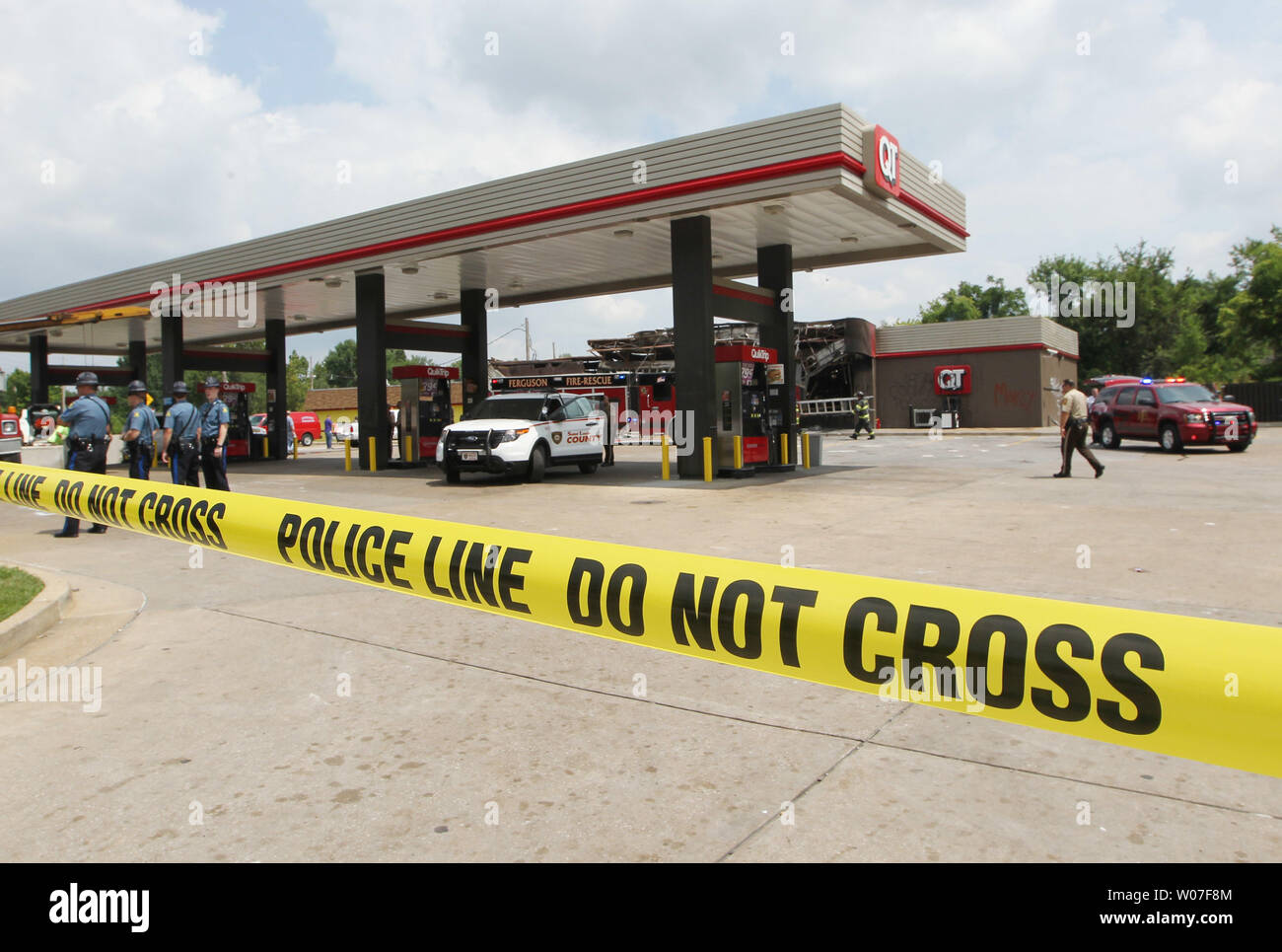 Firefighters and police remain at the scene of the burnt out QuikTrip Gas station following a night of looting, rioting and arsons in Ferguson, Missouri on August 11, 2014. People are upset because of the Ferguson Police shooting and death of an unarmed black teenager Michael Brown on August 9, 2014. In all about 20 businesses sustained damage after a candlelight vigil turned violent.   UPI/Bill Greenblatt Stock Photo