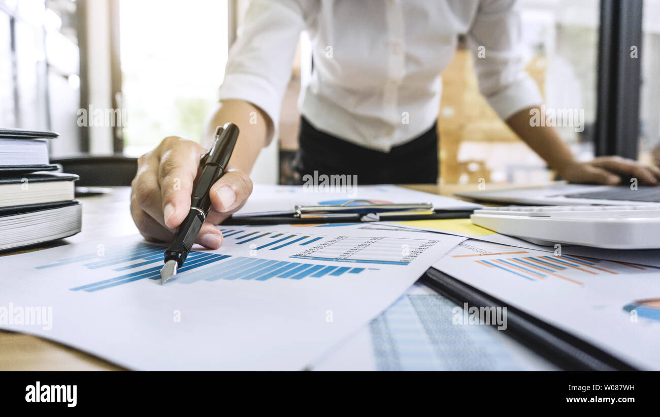 Business woman accountant working and calculating financial data on graph documents, doing finance in workstation. - Stock Image