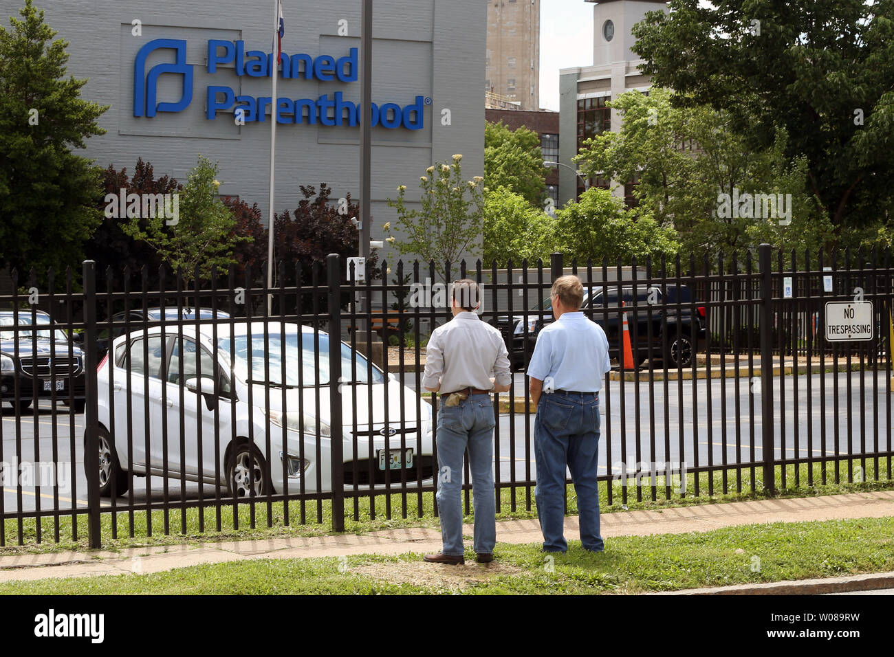 Men stand quietly, praying outside the fence of the Planned
