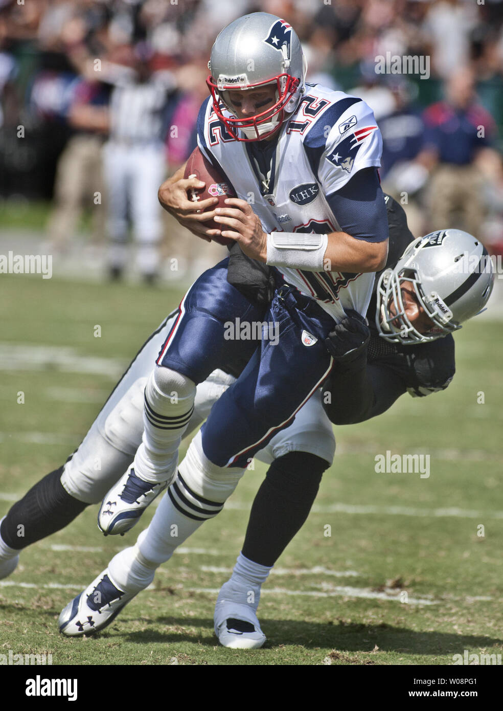 New England Patriots QB Tom Brady (12) is sacked by Oakland Raiders Richard Seymour in the first quarter at the Coliseum in Oakland, California on October 2, 2011.  Seymour was flagged for unnecessary roughness on the play.      UPI/Terry Schmitt Stock Photo