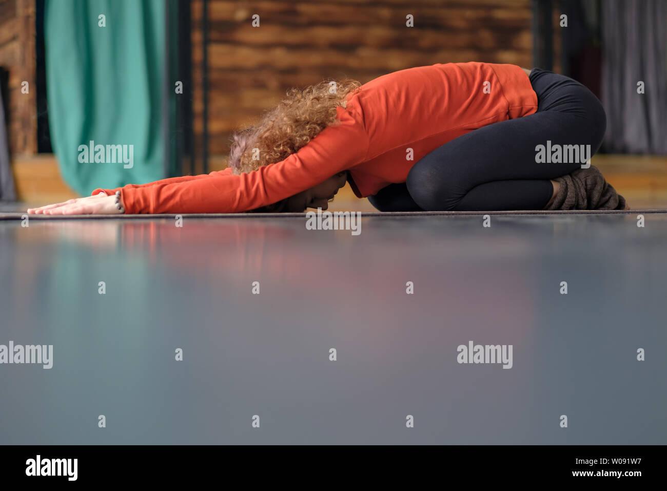 Young woman practicing yoga, doing Child exercise, Balasana pose. - Stock Image