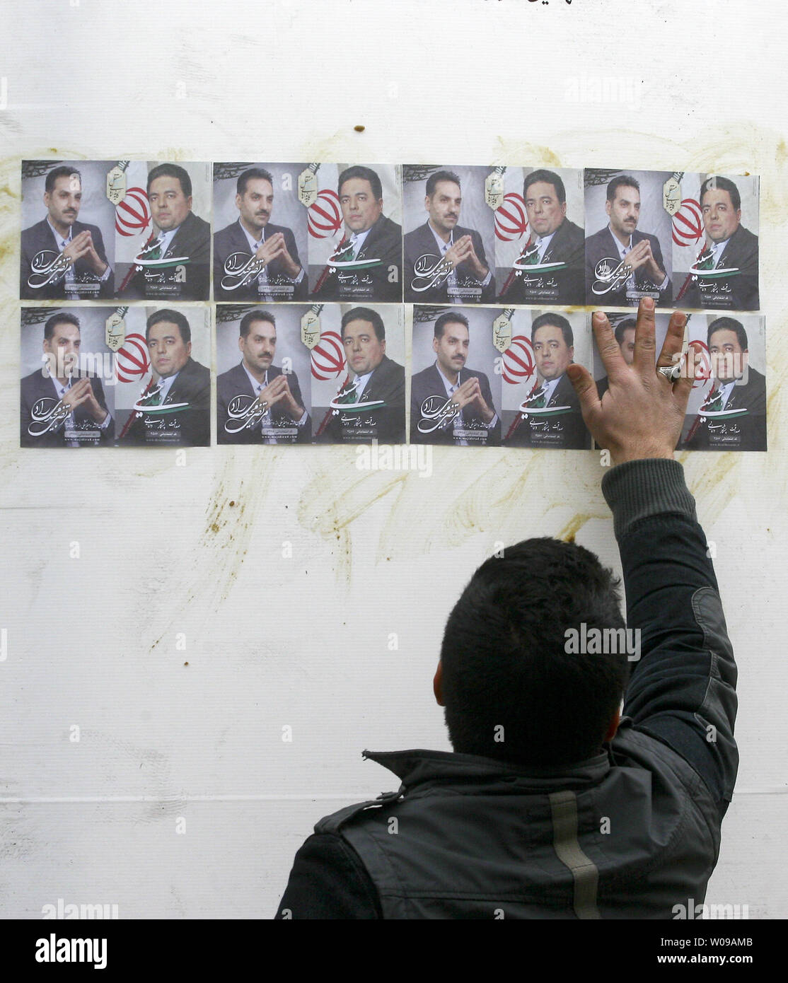 An Iranian man pastes up  posters of two  parliamentary candidates in Tehran, Iran on February 25, 2012.  Iranians prepare themselves for upcoming election on March 2, 2012. The Guardian Council has approved the eligibility of 3,400 candidates for the parliamentary elections.   UPI/Maryam Rahmanian Stock Photo