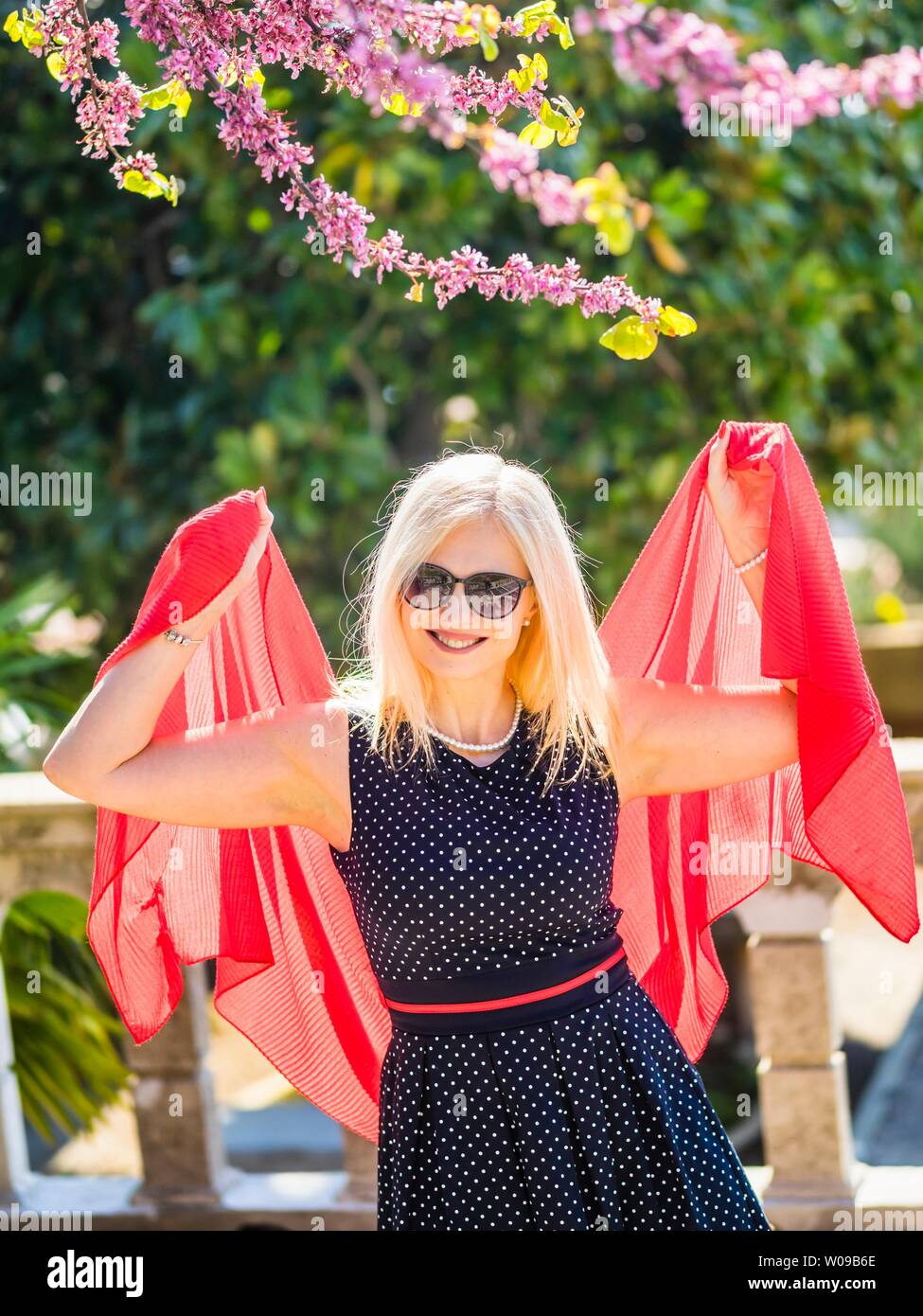 Attractive blonde woman in natural environment mid-day sunshine sunlight spreading hands apart Red robe fabric under Pink flowers in garden smiling Stock Photo