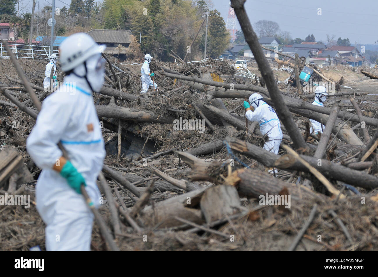 Japanese police wearing chemical protection suits search for victims inside the 20 kilometer radius around the Fukushima Dai-ichi nuclear power plant in Minamisoma, Fukushima prefecture, Japan, on April 15, 2011. A massive earthquake and ensuing tsunami on March 11 destroyed homes, killed thousands and caused a nuclear disaster.    UPI/Keizo Mori - Stock Image