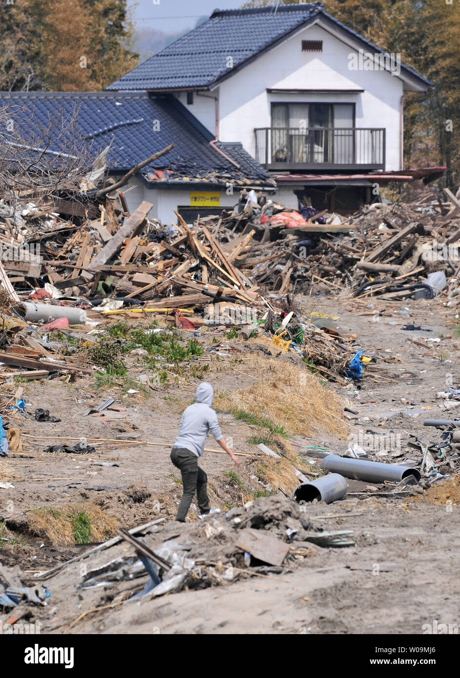 A woman walks through the destruction in Minamisoma, Fukushima prefecture, Japan, on April 15, 2011. A massive earthquake and ensuing tsunami destroyed homes, killed thousands and caused a nuclear disaster.    UPI/Keizo Mori - Stock Image