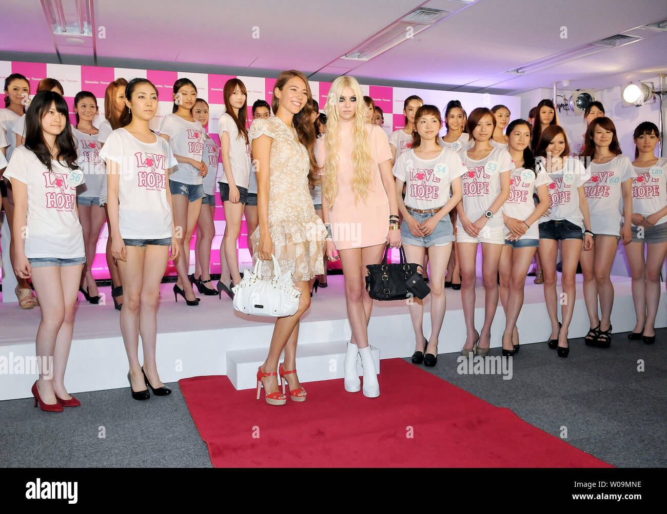 Actress Taylor Momsen (Front, L4) and Japanese model Jessica Michibata (Front, L3) pose with Japanese models for camera during a event at the head office of Samantha Thavasa Japan Limited in Tokyo, Japan on June 18, 2011.     UPI/Keizo Mori - Stock Image