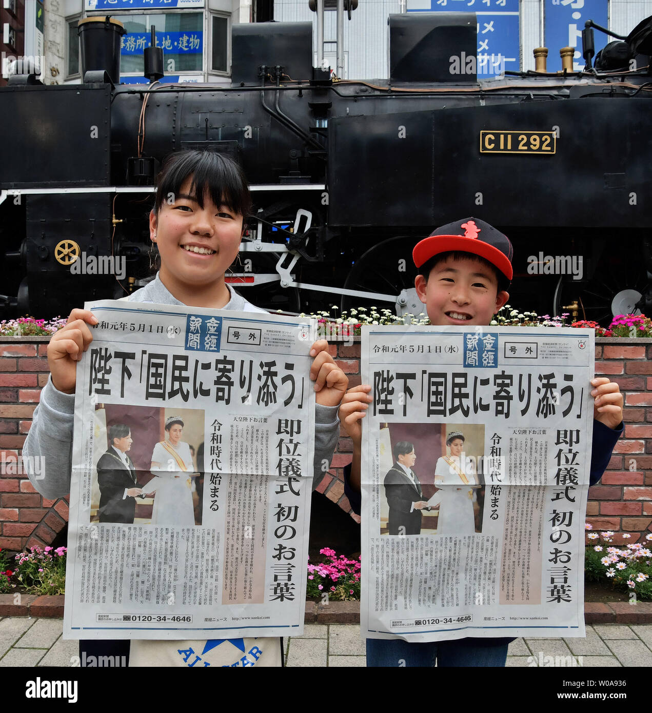 People receive the extra edition of newspaper reporting about the new emperor Naruhito ascends enthroned the Chrysanthemum Throne near the Shinbashi station in Tokyo, Japan on May 1, 2019.     Photo by Keizo Mori/UPI Stock Photo