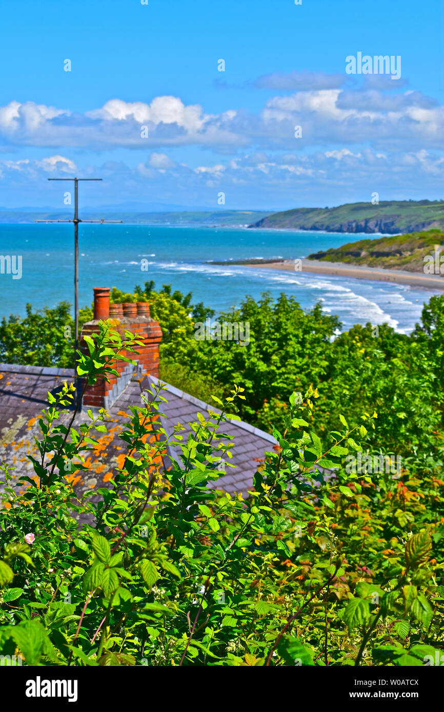 The stunning view from Newquay northwards along Cardigan Bay showing the beautiful coastline curving away in the distance,with waves rolling in. - Stock Image