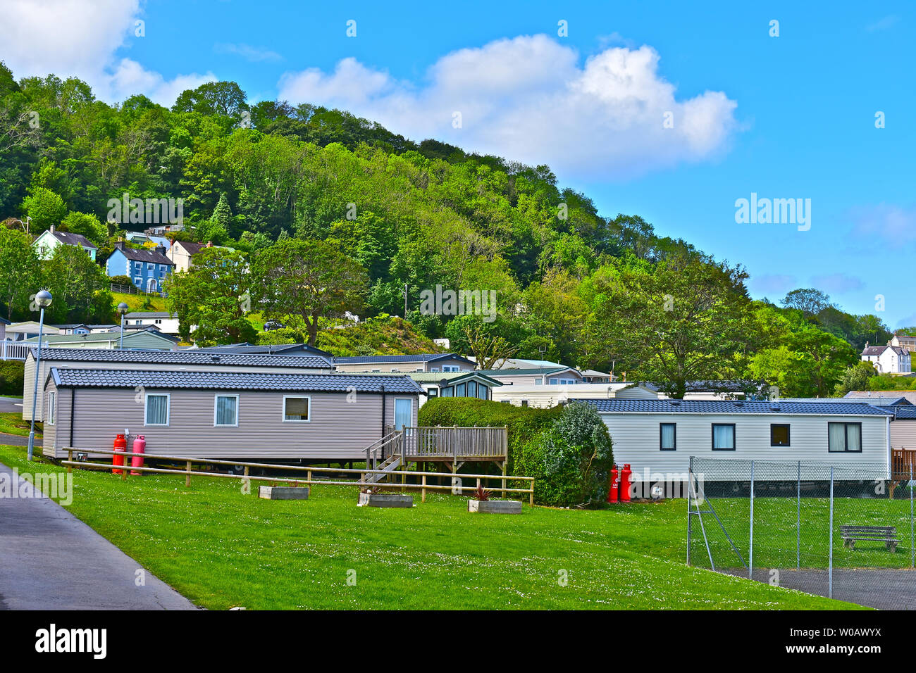 A view of static holiday caravans which overlook Cardigan Bay near Newquay in West Wales.Blue skies & white clouds. Attractive wooded background. - Stock Image
