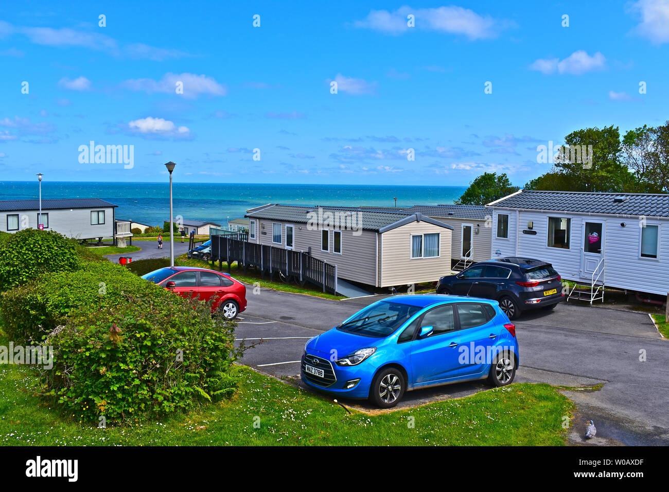 A view of static holiday caravans which overlook Cardigan Bay near Newquay in West Wales.Blue skies & white clouds. Cars parked nearby. - Stock Image
