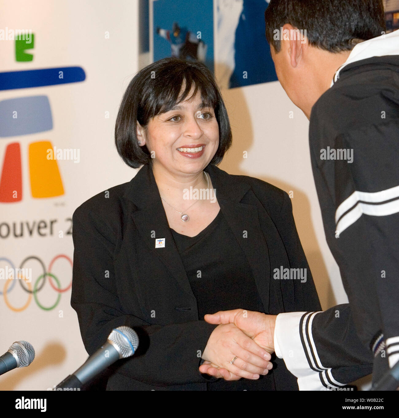 Logo designer Elena Rivera MacGregor (L.) shakes hands with Paul Okalik, Premier of the territory of Nunavut at a press conference after the unveiling of Vancouver 2010's new Olympic emblem 'Ilanaaq' an inukshuk during a ceremony held at Vancouver's GM Place, April 23, 2005.   ( UPI Photo / Heinz Ruckemann ) - Stock Image