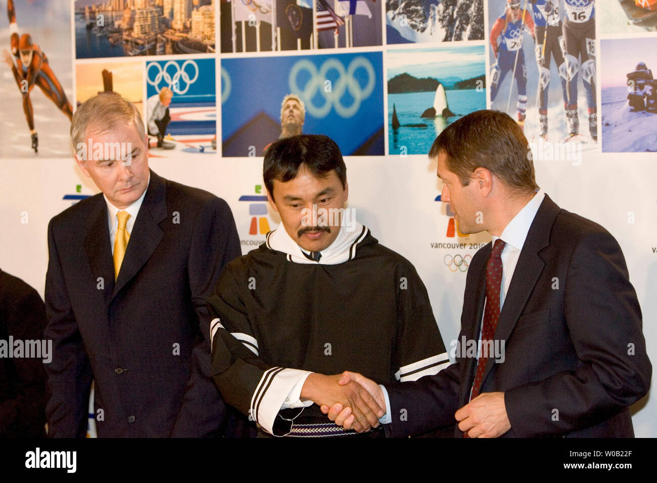 VANOC CEO John Furlong (l.) looks on as Director IOC Television and Marketing Services, Timo Lumme (r.) shakes hands with Paul Okalik, Premier of the territory of Nunavut at a press conference after the unveiling of Vancouver 2010's new Olympic emblem 'Ilanaaq' an inukshuk during a ceremony held at Vancouver's GM Place, April 23, 2005.   (UPI Photo / Heinz Ruckemann) - Stock Image