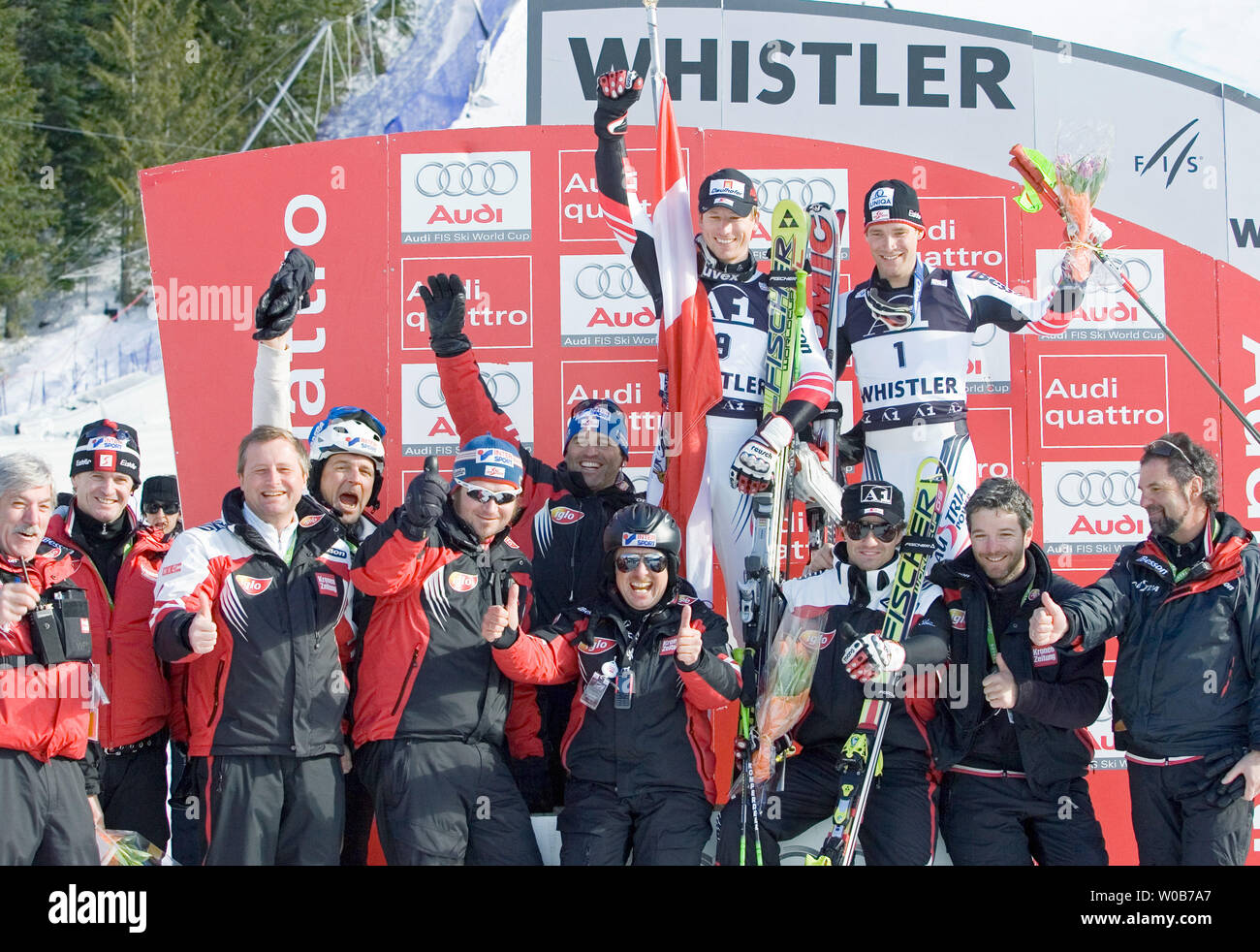 Celebrating on the podium are first place Hannes Reichelt from Austria (top L) with third place teammate Benjamin Raich (top R), along with coaching staff and crew from the Austrian ski team in the men's Giant Slalom of Telus presents FIS World Cup Skiing at Whistler, British Columbia, February 23, 2008. The races are also testing conditions for alpine skiing events at Whistler for the 2010 Winter Olympics. (UPI Photo/Heinz Ruckemann) Stock Photo