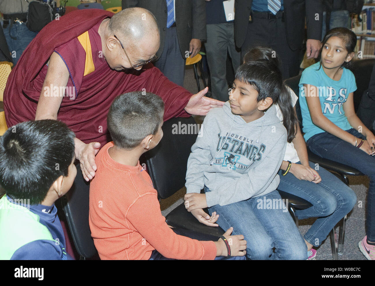 The Dalai Lama greets children as he arrives for his Heart-Mind Youth Dialogue with teachers and students at John Oliver Secondary School in Vancouver, British Columbia, October 21, 2014. The Dalai Lama will be holding meetings over several days during this Vancouver visit.  UPI/Heinz Ruckemann - Stock Image