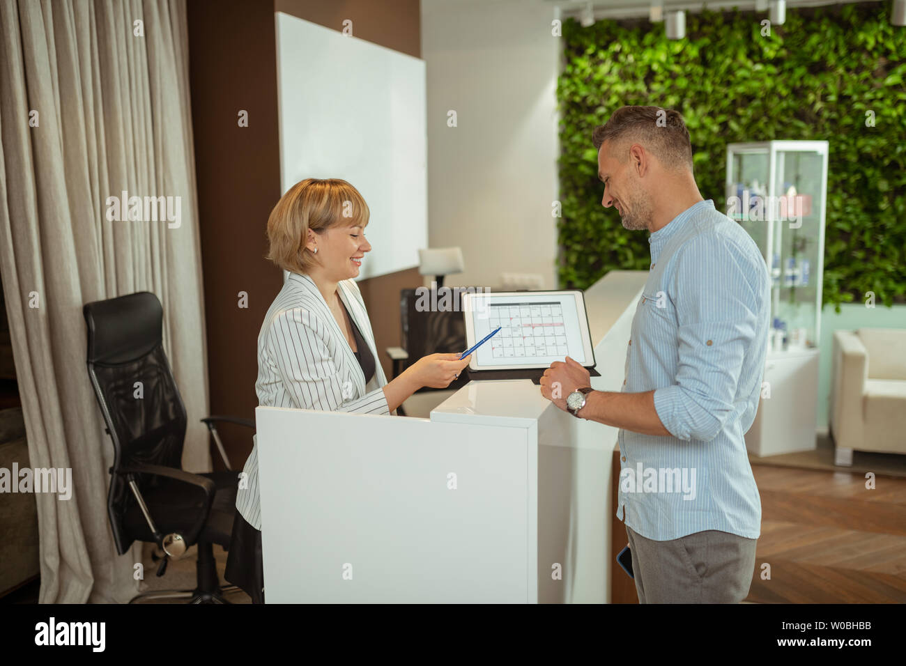 Administrator talking to client and scheduling next meeting - Stock Image