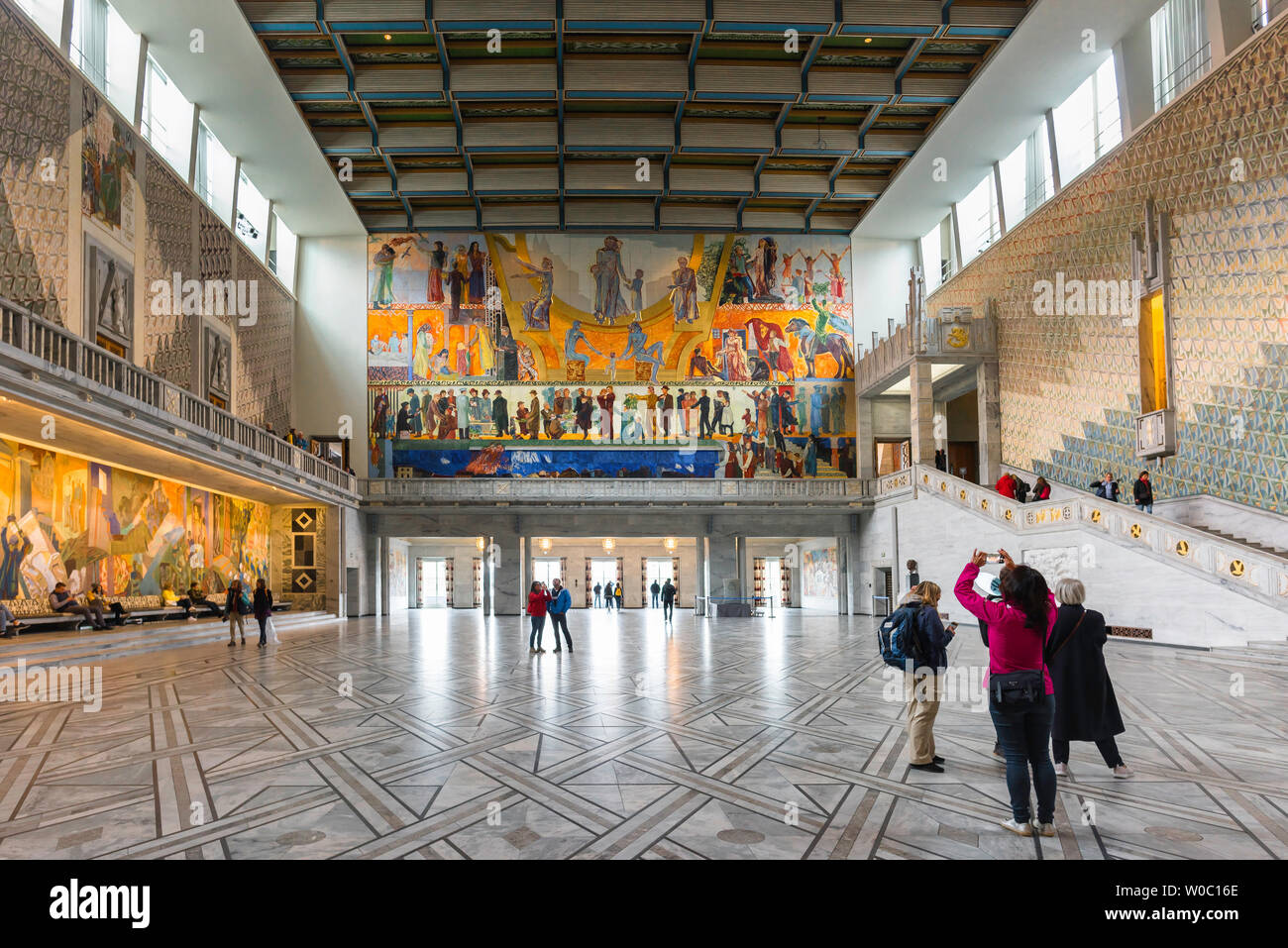 Oslo City Hall, rear view of a young woman taking a photo of the Henrik Sorensen painting inside the Great Hall in Oslo City Hall (Radhus), Norway. Stock Photo