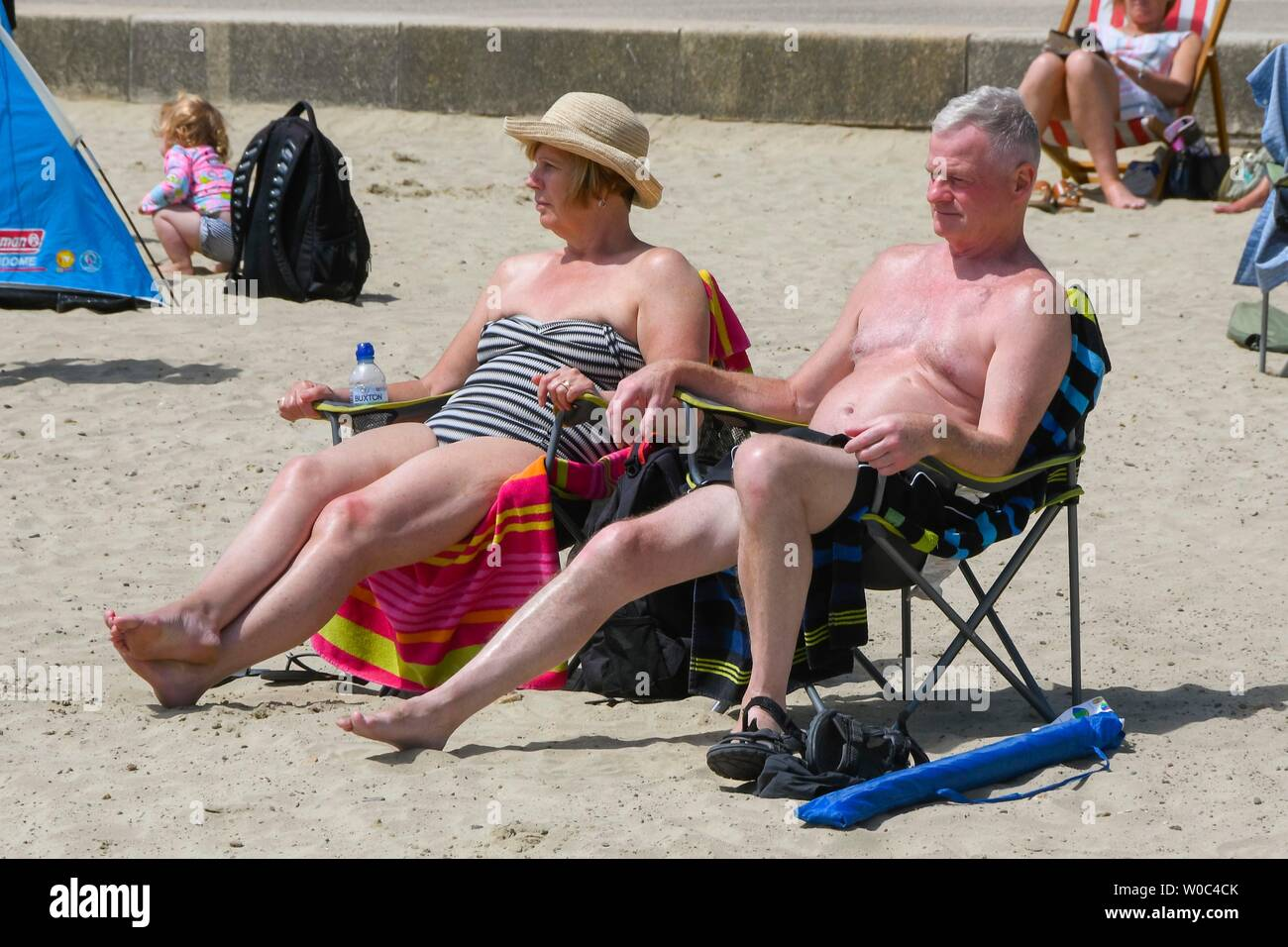 Lyme Regis, Dorset, UK.  27th June 2019. UK Weather.  Sunbathers on the beach at the seaside resort of Lyme Regis in Dorset enjoying a day of clear blue skies and scorching sunshine.   Picture Credit: Graham Hunt/Alamy Live News Stock Photo