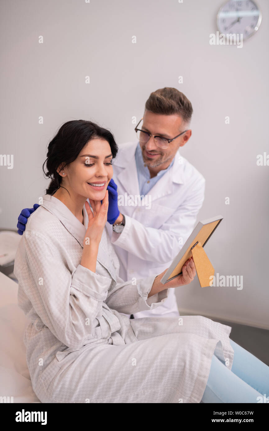 Beautiful businesswoman feeling satisfied after anti-aging procedures - Stock Image
