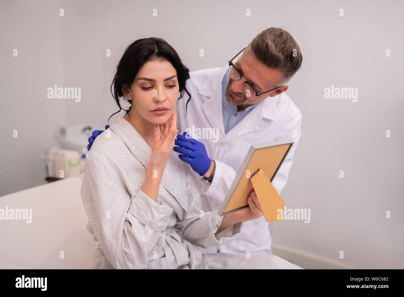 Woman looking into mirror after anti-aging procedures - Stock Image