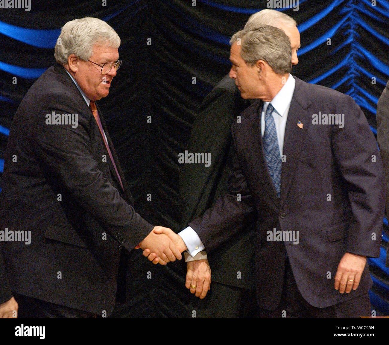 President George W. Bush, right, shakes hands with House Speaker Dennis Hastert, R-IL, before signing a bill banning partial birth abortions on November 5, 2003, in Washington. Behind President Bush is Sen. Orrin Hatch, R-UT. (UPI/Roger L. Wollenberg) Stock Photo