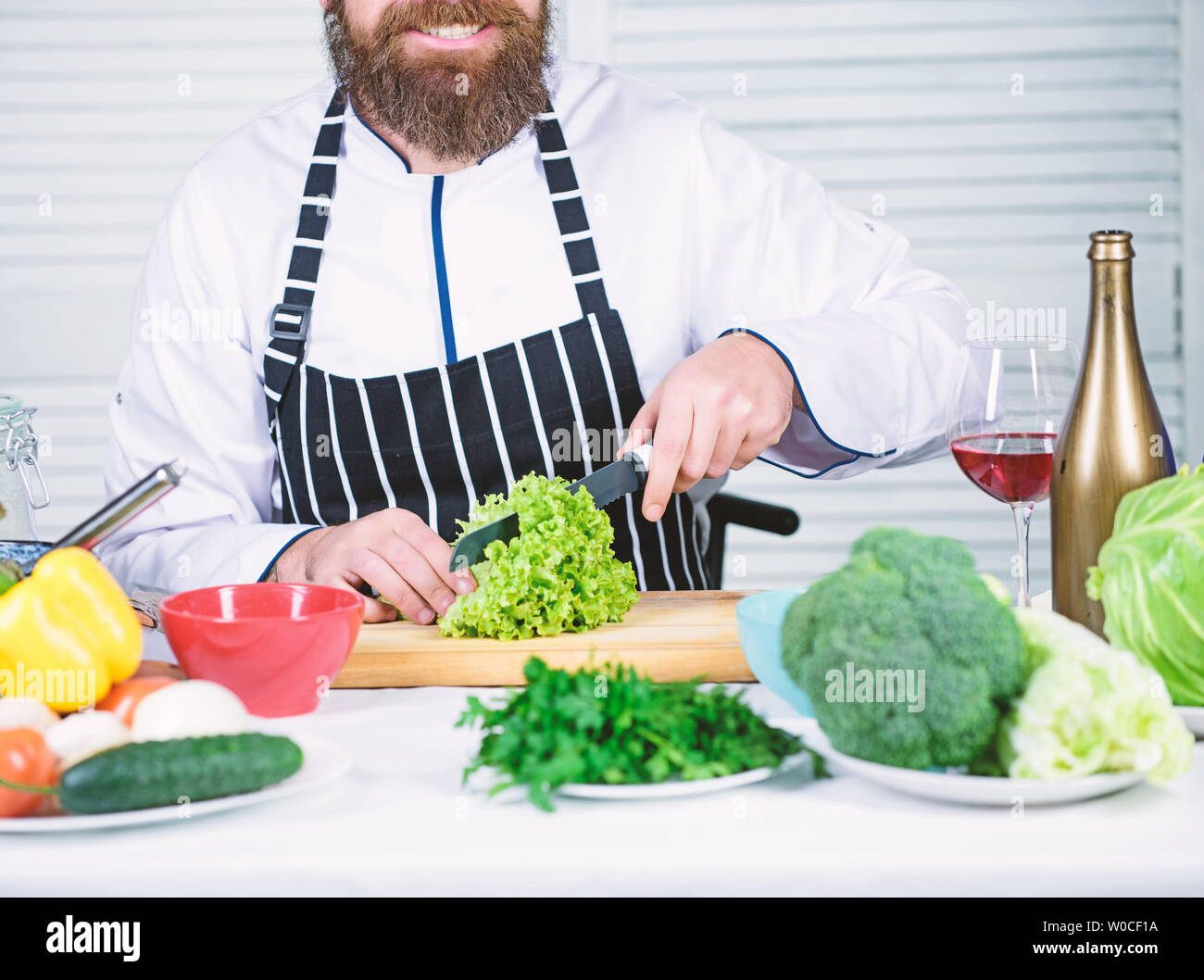Useful for significant amount of cooking methods. Basic cooking processes. Man master chef or amateur cooking food. Sharp knife chopping vegetable. Prepare ingredient for cooking. According to recipe. - Stock Image