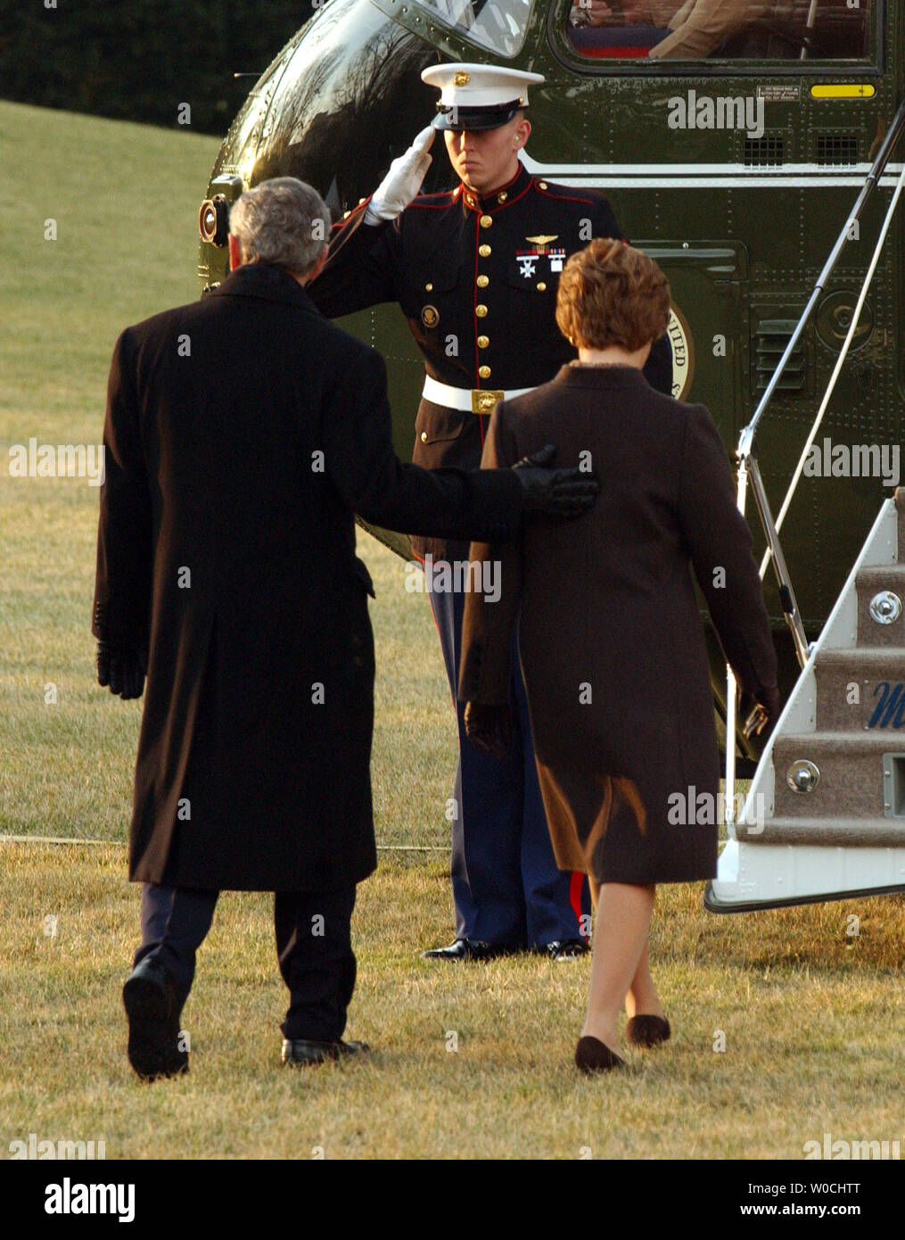 A Marine salutes as U.S. President George W. Bush and First Lady Laura Bush prepare to embark on Marine One on the South Lawn of the White House on Feb. 20, 2005. Bush is en route to Brussels, Belgium, for meetings with world leaders.   (UPI Photo/Roger L. Wollenberg) - Stock Image