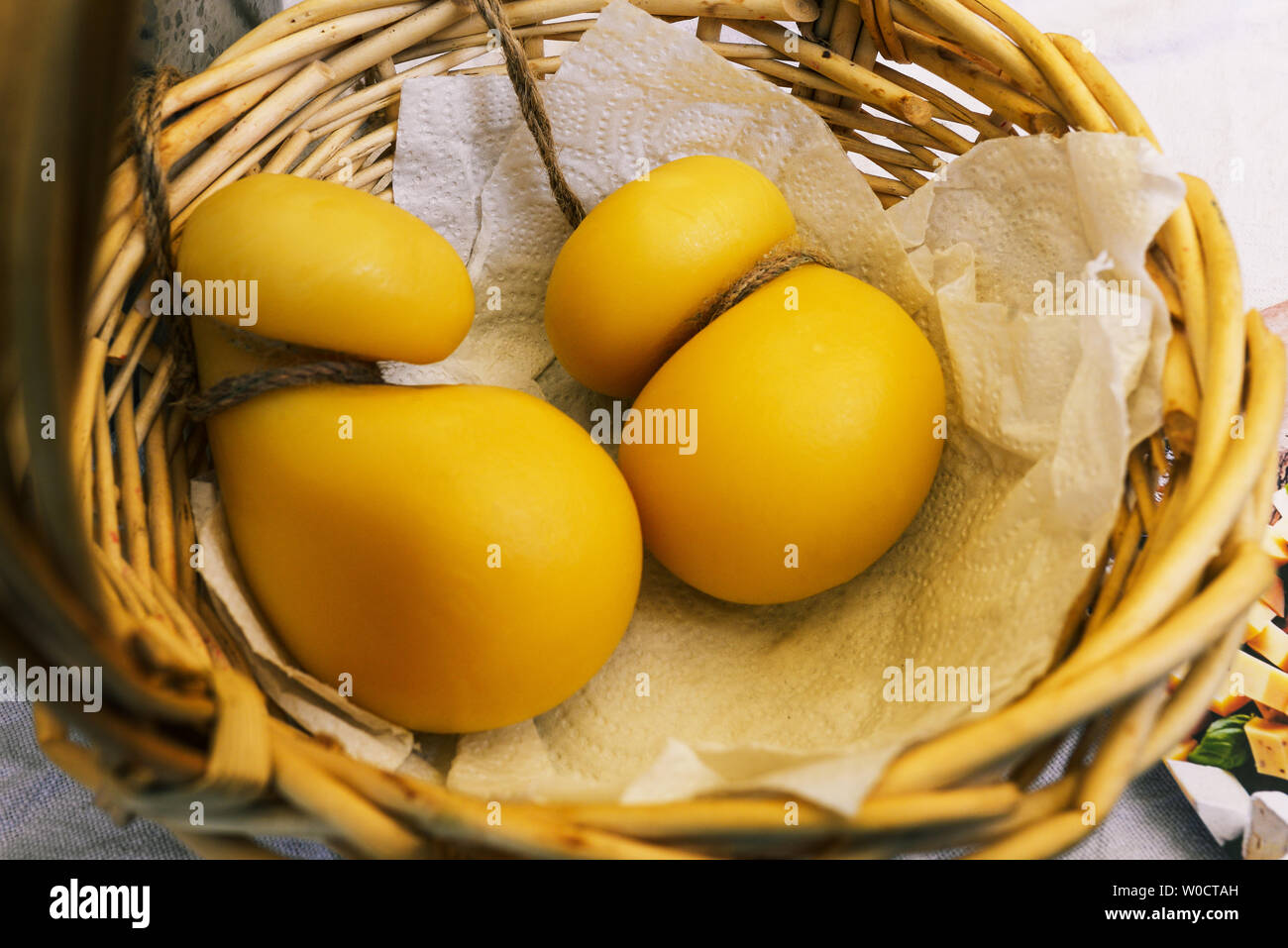 Two yellow cheese heads in a basket. Oval-shaped hard cheese tied with a rope. Production and sale of cheese. Organic Product - Stock Image