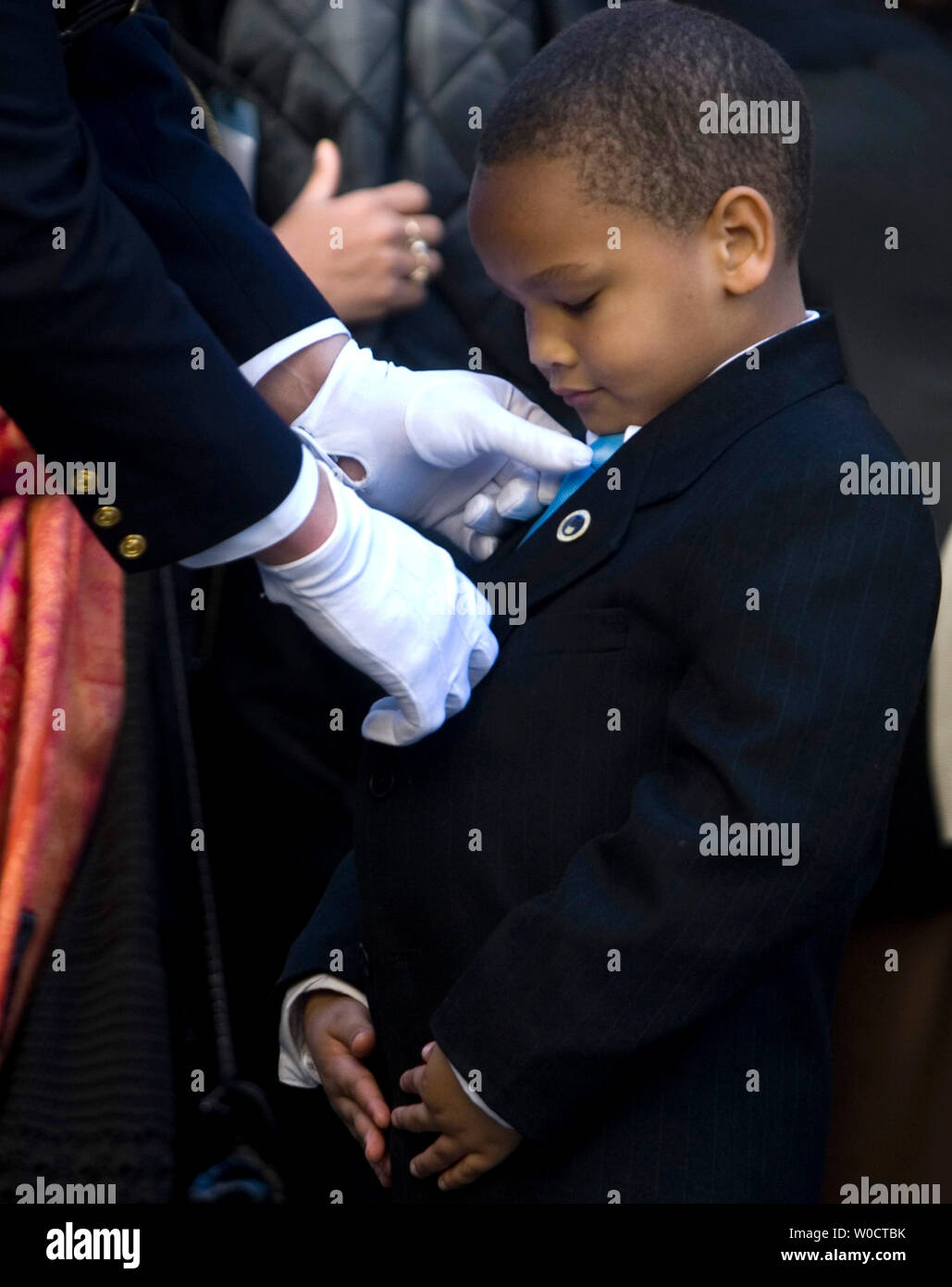 An officer helps Rosa Parks great nephew Schuyler McCauley Brown with his tie before the funeral service for Parks at the Metropolitan AME Church October 31, 2005 in Washington, DC. More than 30,000 people at the U.S. Capitol Rotunda passed by the casket of the woman who refused to give up her seat to a white man on a Montgomery, Alabama city bus in 1955, sparking the American civil rights movement. (UPI Photo/Kamenko Pajic) Stock Photo