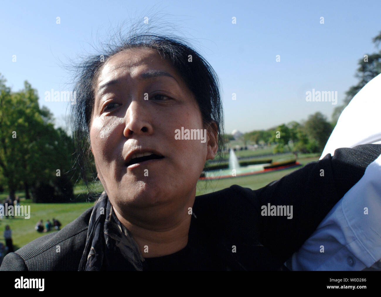 An unidentified woman is removed from the press riser, after screaming and waving a flag as U.S. President George W. Bush and Chinese President Hu Jintao participate in a south lawn arrival ceremony at the White House on April 20, 2006. (UPI Photo/Kevin Dietsch) - Stock Image