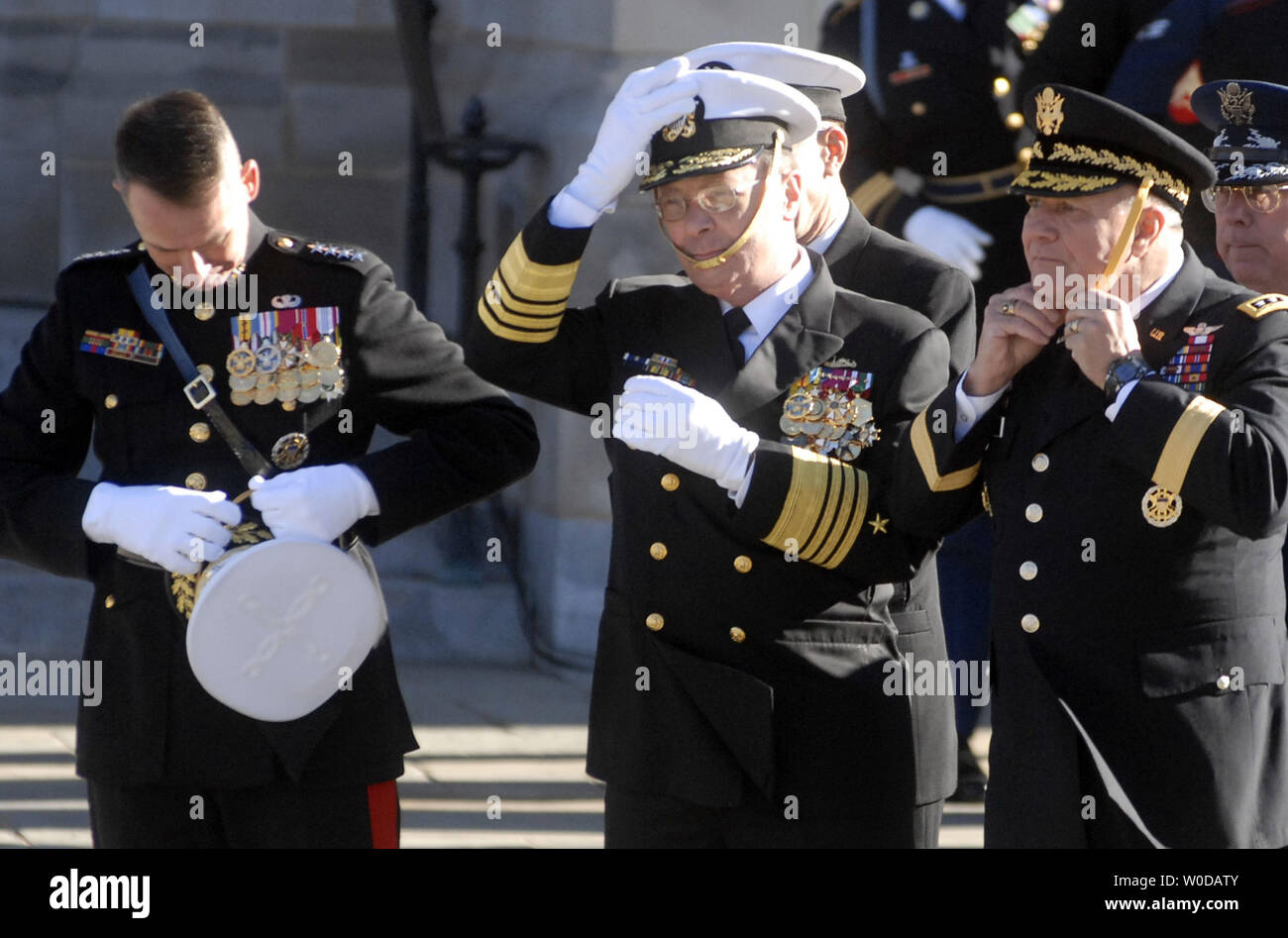The Chairman of the Joint Chiefs of Staff Gen. Peter Pace (L), Vice Chairman of the Joint Chiefs of Staff Adm. Edmund Giambastiani (C)and Vice Chief of staff of the US Army Gen. Richard Cody (R) attempt to secure their hats as a strong wind blows during the state funeral for former President Gerald Ford at the National Cathedral in Washington on January 2, 2007. (UPI Photo/Kevin Dietsch) - Stock Image