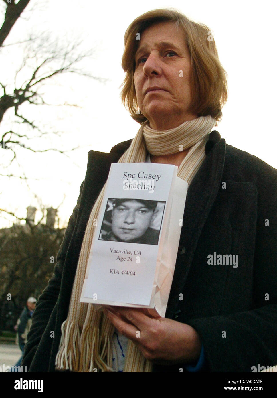 Cindy Sheehan listens to a protester read the names of 3000 American soldiers who died serving in the Iraq War while holding a paper bag with an illuminated candle outside the White House in Washington on January 3, 2007. The photograph on the bag is her son, Casey Sheehan, who died while serving in Iraq in 2004.  (UPI Photo/Alexis C. Glenn) Stock Photo