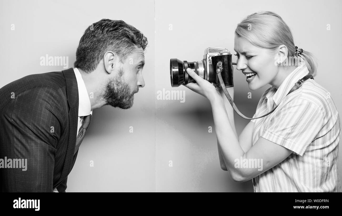 He is photogenic. Pretty woman using professional camera. Businessman posing in front of female photographer. Photographer shooting male model in studio. Fashion shooting in photo studio. Stock Photo